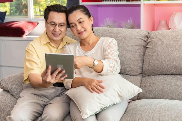 Het hogere paar aziatische teruggetrokken kijken tablet in verpleeghuis.