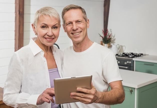 Het hogere paar dat van smiley hun tablet houdt