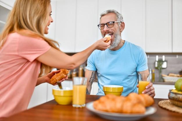 Het hogere paar heeft ontbijt. de vrouw geeft haar man een croissant en heeft 's ochtends vroeg plezier met hem in de keuken.