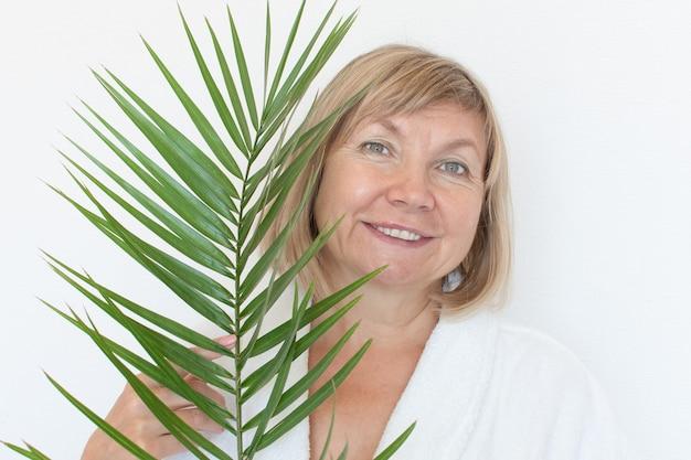 Het hogere vrouw glimlachen anti-leeftijdsconcept met palmblad. rijp womagezicht na kuur. ouderdom in vreugde, kliniek voor plastische chirurgie, schatje grootmoeder, cosmetologie, nieuwe senior, gepensioneerde, volwassen mensen