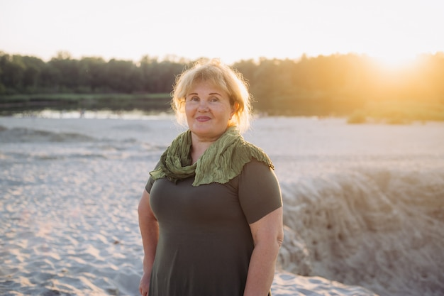 Het hogere vrouw glimlachen die zich op strand op zonsondergang bevinden