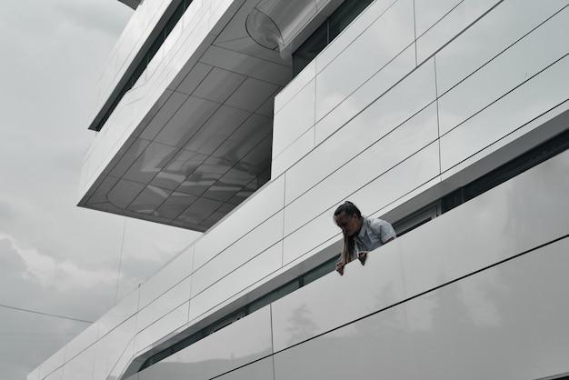 Het hoofd en de schouders van het meisje op de achtergrond van het gebouw. geometrie in de bouw.
