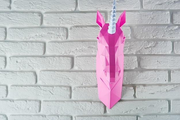 Het hoofd van de roze eenhoorn van document het hangen op witte bakstenen muur wordt gemaakt die.