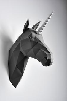 Het hoofddocument van de zwarte geometrische eenhoorn die op grijze in de schaduw gestelde muur hangen.