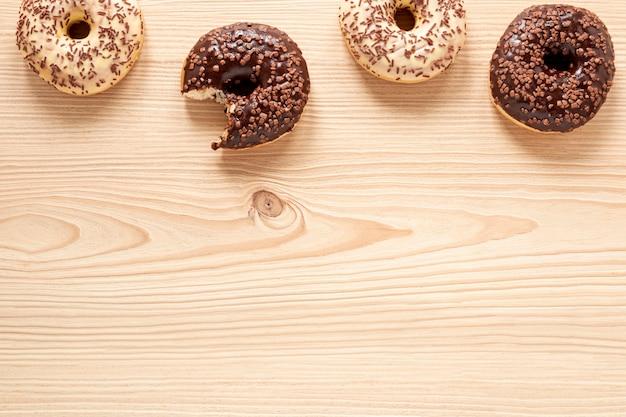 Het hoogste kader van het meningsvoedsel met donuts en houten achtergrond