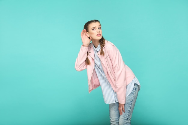 Het horen van nieuwsgierig portret van een mooi schattig meisje met make-up en bruin vlechtkapsel in een gestreept lichtblauw shirt roze jas. binnen, studio-opname geïsoleerd op blauwe of groene achtergrond.