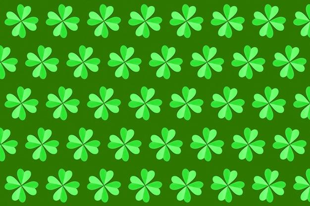 Het horizontale groene natuurlijke patroon van de bladerenklaver met de hand gemaakt van gekleurd document op een groene muur. gelukkig st.patrick's day-concept.