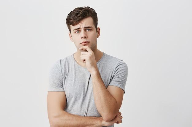 Het horizontale portret van knap jong gekleed mannetje houdt terloops de hand onder de kin, fronst zijn gezicht, kijkt verbaasd, luistert naar iemands officiële toespraak, analyseert informatie. mensen en levensstijl