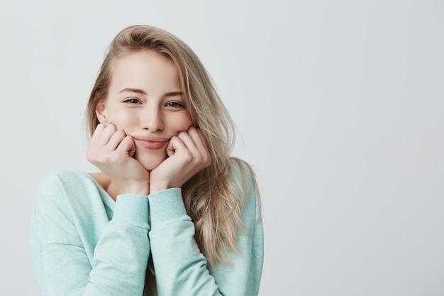 Het horizontale portret van positief kaukasisch vrouwelijk model met blond haar dat haar hoofd op handen laat rusten, ziet er dromerig uit
