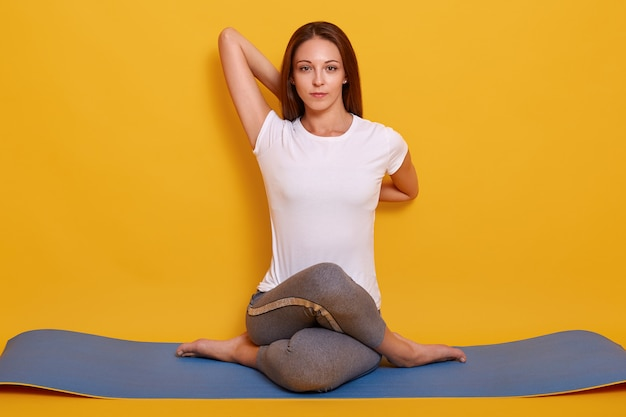 Het horizontale schot van flexibel meisje dat yoga doet stelt geïsoleerd over geel