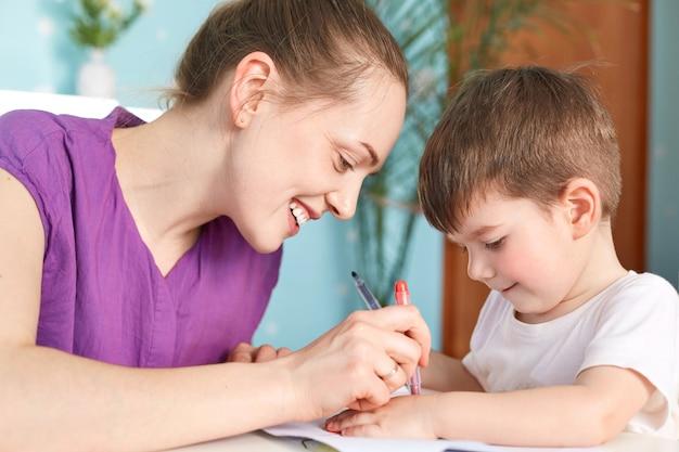 Het horizontale schot van gelukkige jonge glimlachende moeder die blij zijn om vrije tijd met haar kleine zoon door te brengen, trekt iets met grote belangstelling