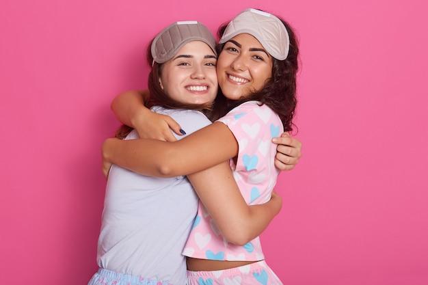 Het horizontale schot van mooie meisjes kleedde slaapmaskers en pyjama's