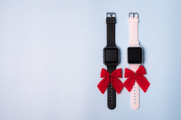 Het horloge is wit en zwart elektronisch met een strik op een effen achtergrond