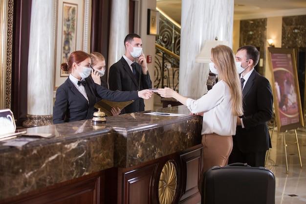 Het hotelpersoneel bedient gasten met medische maskers