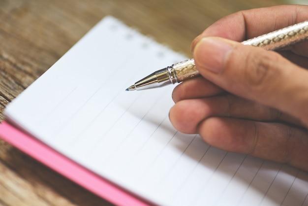 Het houden van een pen op schetsboek of notebook blanco pagina's op rustiek hout. notebook papier zakelijke kantoorbenodigdheden of onderwijs concept