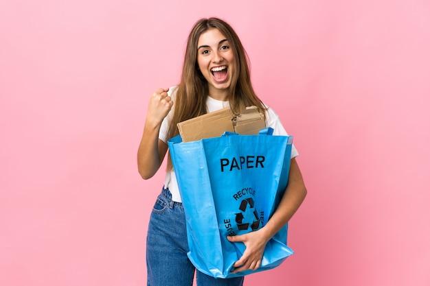 Het houden van een recycling zak vol papier om te recyclen op geïsoleerde roze viert een overwinning