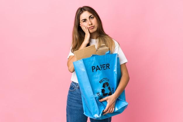 Het houden van een recycling zak vol papier te recyclen over geïsoleerde roze ongelukkig en gefrustreerd