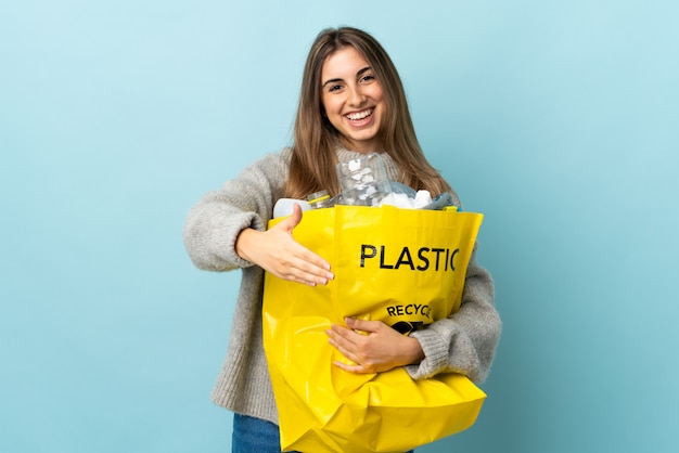 Het houden van een zak vol plastic flessen te recyclen over geïsoleerde blauwe handshaking na een goede deal