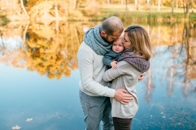 Het houdende van familiepaar koestert hun kind bij aard