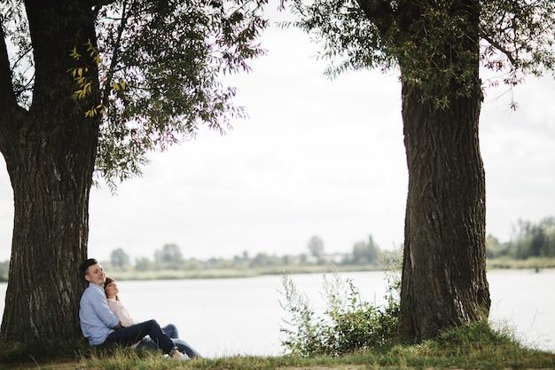 Het houdende van jonge paar koestert en glimlacht in openlucht dichtbij het meer op zonnige dag. liefde en tederheid, dating, romantiek, familieconcept.