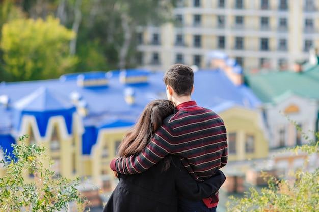 Het houdende van paar omhelst elkaar en bekijkt stad