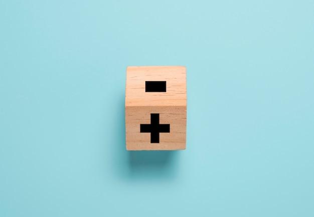 Het houten kubusblok omdraaien om het minteken in het plusteken op de blauwe tafel te veranderen. positief denken en mentaliteitsconcept.