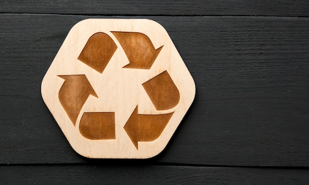 Het houten recycling-pictogram op de tafel