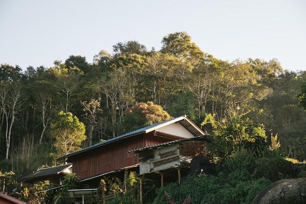 Het huis van de dorpsbewoner met bomen en bergen op de achtergrond.