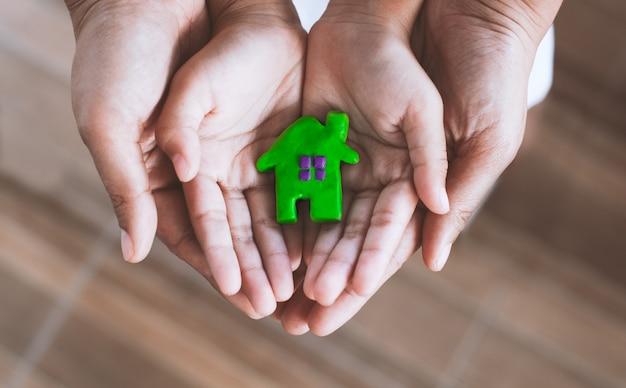 Het huis van de plasticineklei op kind en oudershanden. gelukkige familie en warm huisconcept.