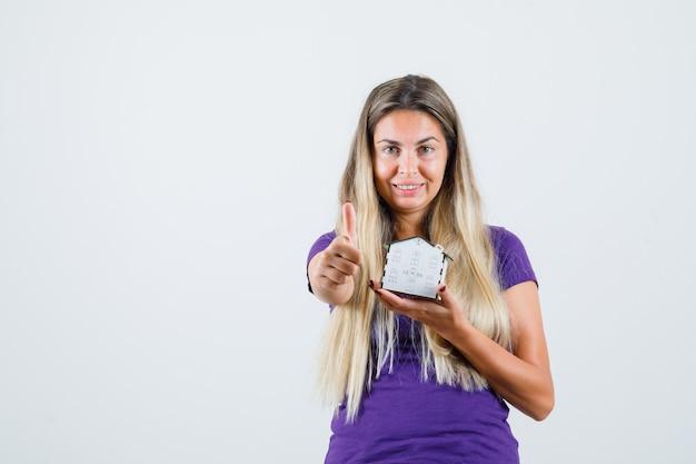 Het huismodel van de jonge dameholding, die duim in violet t-shirt toont en vrolijk kijkt. vooraanzicht.