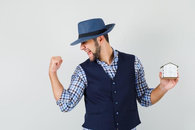 Het huismodel van de jonge mensenholding, winnaargebaar in overhemd, vest, hoed toont en gelukkig kijkt. vooraanzicht.