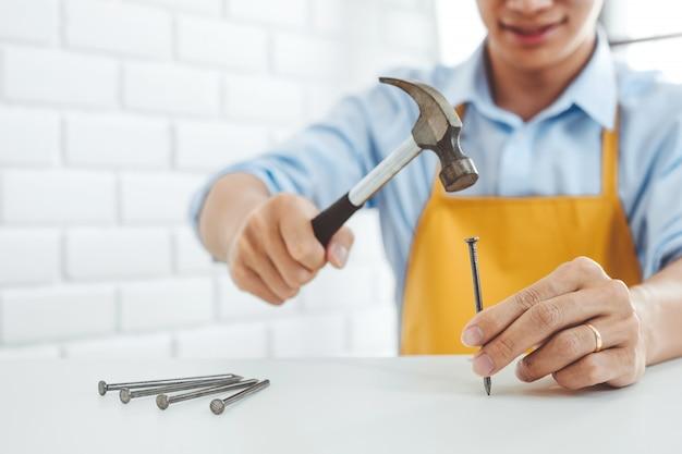 Het huisverbetering van de aziatische mens het assembleren van meubilair leest instructies en gebruikt hamer om spijker in het hout te steken.