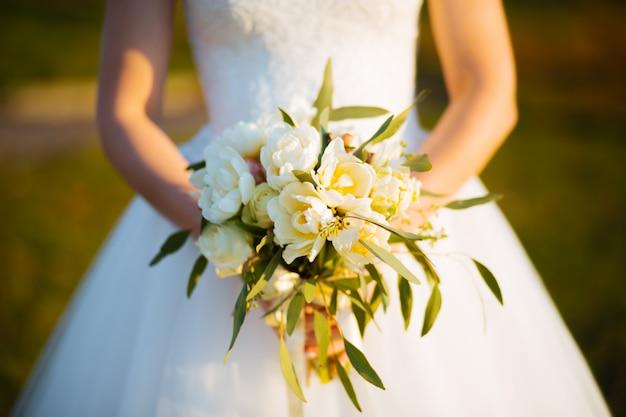 Het huwelijk bloeit rozenboeket in bruidhanden met witte kleding op ruimte