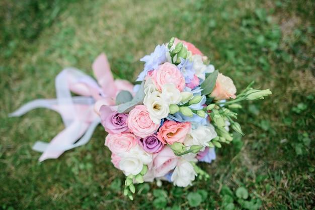 Het huwelijksboeket dat van roze rozen en groene knoppen wordt gemaakt ligt op het gazon