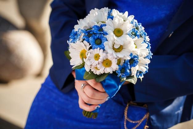 Het huwelijksboeket houdt de bruid in handen