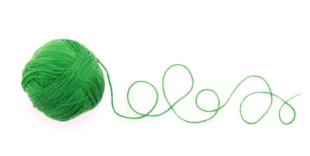 Het idee is een verwarde draad. groene bol garen op wit