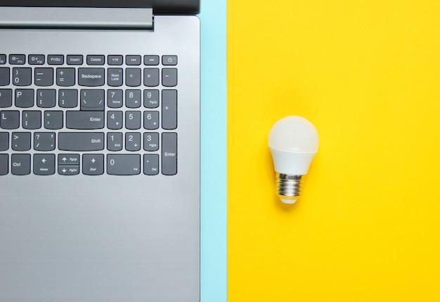 Het idee van een bedrijfsconcept. laptop en gloeilamp op een blauw-gele tafel. bovenaanzicht