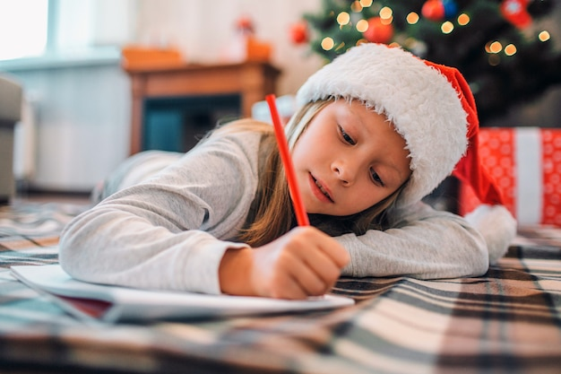 Het ijverige meisje ligt op blenket op vloer en schrijft brief aan kerstman. ze gebruikt rood potlood. meisje is serieus en geconcentreerd. ze is alleen in de kamer. er zijn kerstboom met cadeautjes achter haar.