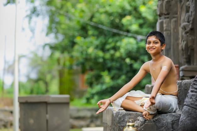 Het indiase priester kind doet meditatie