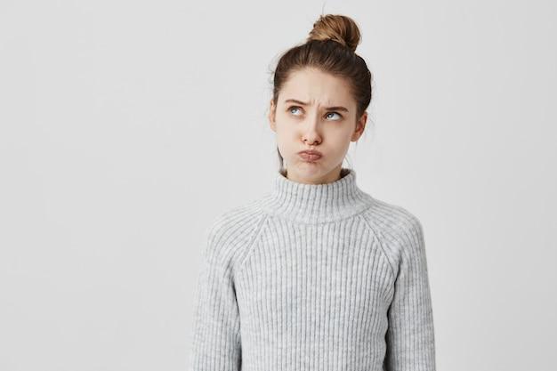 Het infantiele volwassen vrouw dragen toevallig met gezicht die naar omhoog beweren te worden beledigd. mooi meisje dat omhoog blazend haar wangen kijkt die op medelijden drukt. lichaamstaal