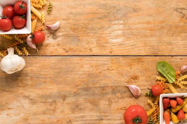 Het ingrediënt van deegwaren bij de hoek van houten achtergrond