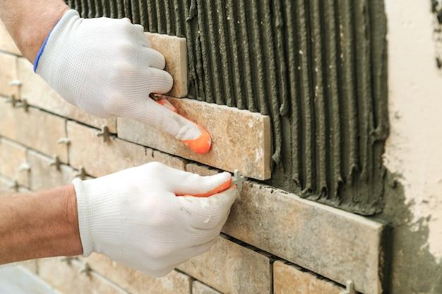Het installeren van de tegels op de muur in de vorm van stenen