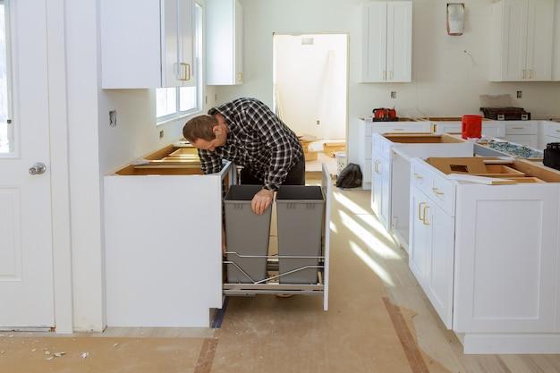 Het installeren van een nieuwe inductiekookplaat in moderne laden vuilnisbak keukeninstallatie