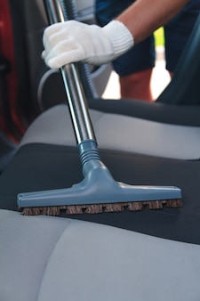 Het interieur van de auto schoonmaken met een stofzuiger