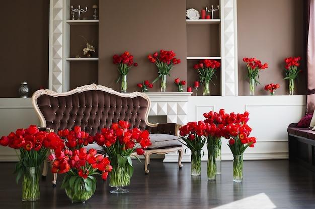 Het interieur van de woonkamer in bruine tinten met grote boeketten rode tulpen in vazen.
