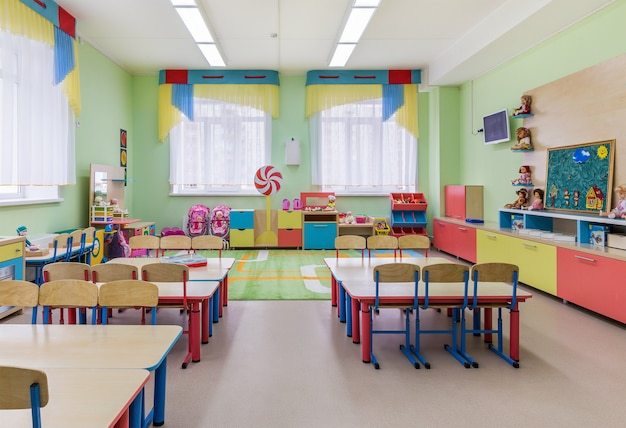 Het interieur van een gezellige grote kamer voor lessen en spelletjes op de kleuterschool.