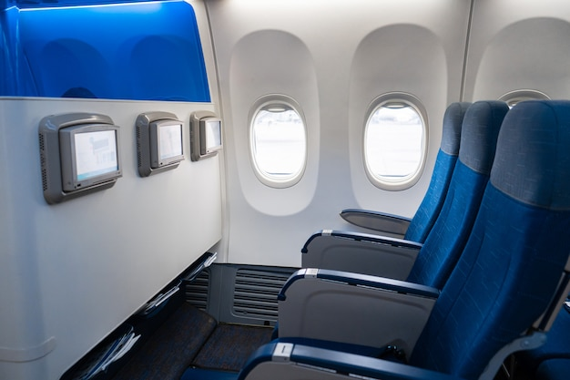 Het interieur van het vliegtuig. lege vliegtuigcabine. rijen passagiersstoelen met schermen in de hoofdsteunen