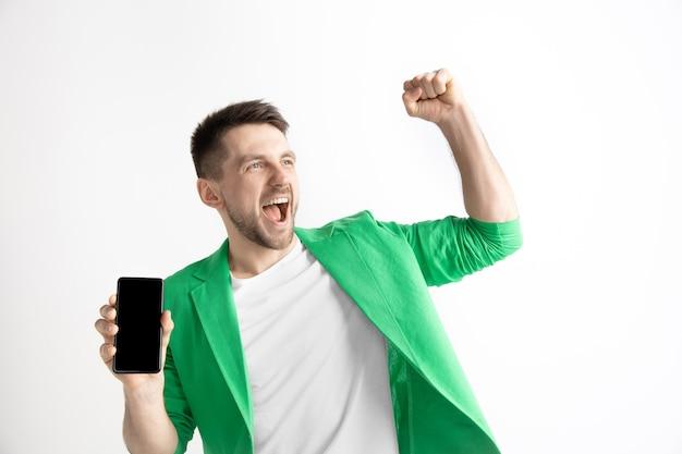 Het is cool. goed nieuws. doe dat zoals ik. jonge knappe man smartphone scherm tonen en ondertekenen ok teken geïsoleerd op een grijze achtergrond. menselijke emoties, gezichtsuitdrukking, reclameconcept.