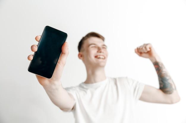 Het is cool. goed nieuws. doe dat zoals ik. jonge knappe man smartphonescherm tonen en ondertekenen ok teken geïsoleerd op een grijze achtergrond. menselijke emoties, gezichtsuitdrukking, reclameconcept.