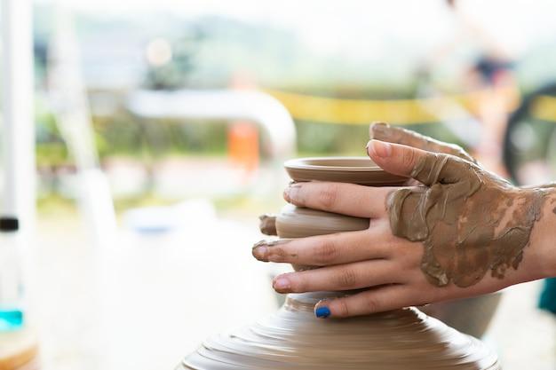 Het is de hand van een kind dat aardewerk maakt.